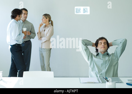 Businessman sitting at desk with hands behind head and eyes closed, colleagues standing in background - Stock Photo