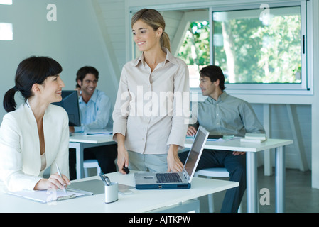 Two young businesswomen smiling at each other in office, male colleagues in background - Stock Photo
