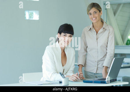 Two young businesswomen in office, one seated at desk, the other standing by her side, both smiling at camera, portrait - Stock Photo