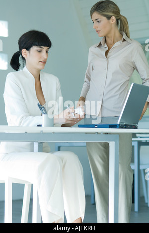 Two young businesswomen in office, one seated at desk, the other standing by her side, having serious discussion - Stock Photo