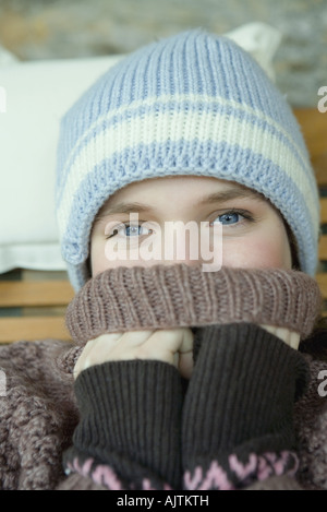 Teen girl covering mouth with turtle neck sweater, portrait - Stock Photo