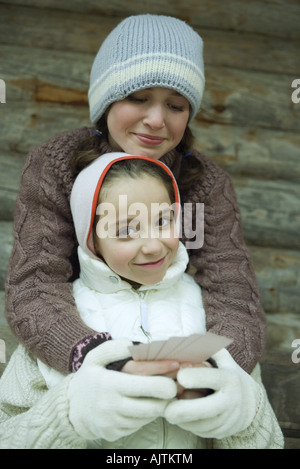 Young friends in winter clothes, one holding cards while the other gives her a hug - Stock Photo