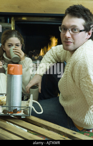 Young man and teen girl drinking hot drinks by fire place - Stock Photo