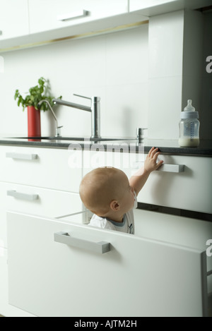 Baby in drawer reaching for bottle on kitchen counter - Stock Photo