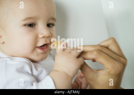Baby taking pacifier from mother's hand, close-up - Stock Photo