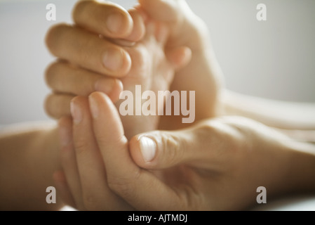Mother's hands holding baby's foot, close-up - Stock Photo