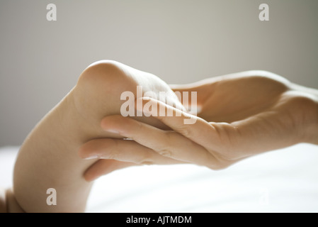 Mother's hand holding baby's foot, close-up - Stock Photo