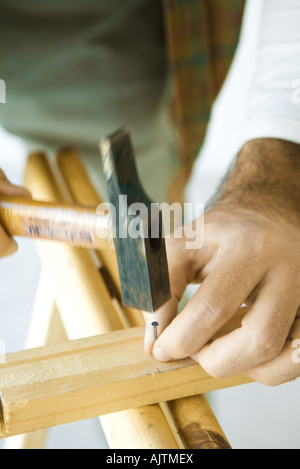 Man hammering nail into piece of wood, close-up of hands - Stock Photo