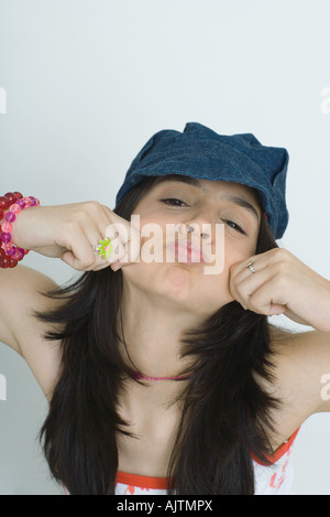 Teenage girl making faces at camera, portrait - Stock Photo