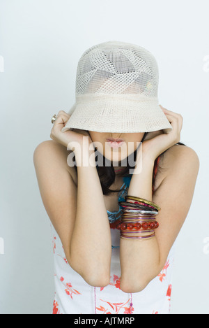 Teenage girl pulling hat down over face, making faces, portrait - Stock Photo