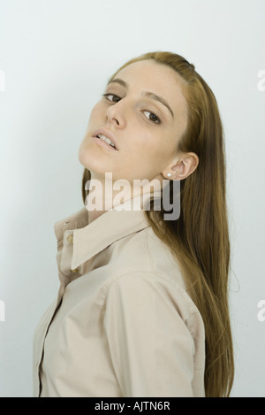Young woman looking at camera, head back, portrait - Stock Photo
