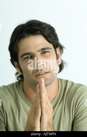 Man pleading with hands together, looking at camera, portrait - Stock Photo