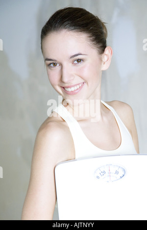 Young woman holding bathroom scale, smiling at camera, portrait - Stock Photo