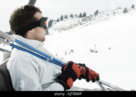Young man taking ski lift - Stock Photo