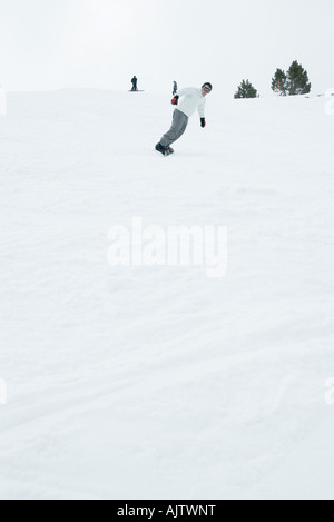 Young man snowboarding, full length - Stock Photo