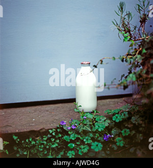 A glass milk bottle on a doorstep in Llanthony, Ewyas Valley, Wales, UK  KATHY DEWITT - Stock Photo