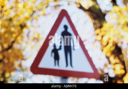 Impressionistic triangular roadsign with autumn foliage behind warning that adults or children may be walking in - Stock Photo