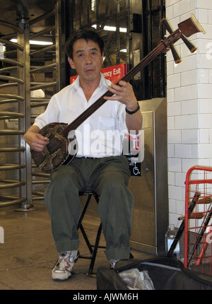 Chinese immigrant playing on a SanXian (three-string) in a subway stations in Chinatown, NYC. - Stock Photo