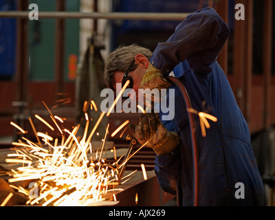 Man cutting metal with a blowtorch in a coachbuilding factory - Stock Photo
