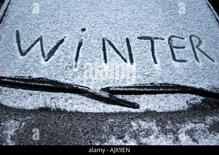 the word winter written in snow on windshield of a car. Photo by Willy Matheisl - Stock Photo