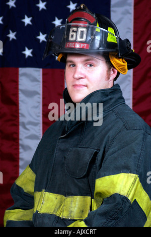 Young Fire Fighter portrait posing in front of the American Flag - Stock Photo
