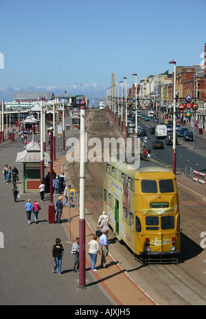 View North along Blackpool promenade shwing tramlines and a tram. - Stock Photo