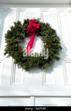 Holiday Christmas Wreath with Red Velvet Ribbon Bow on White Door - Stock Photo