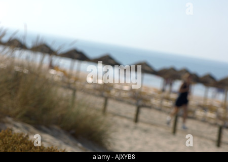 Straw um brellas on the beach and people making jogging exercise on the beach - Stock Photo