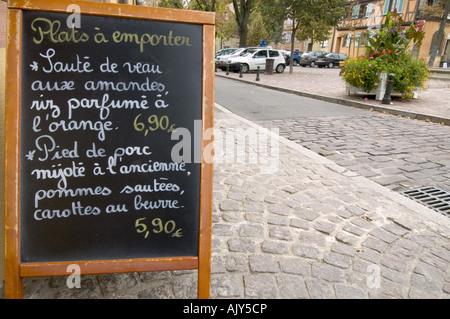 Handwritten restaurant menu by the cobblestone street at Colmar, Alsace, France. - Stock Photo