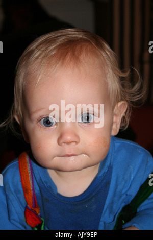 Baby boy aged 11 months, close up, with huge blue eyes, grubby face and dribble due to teething. - Stock Photo