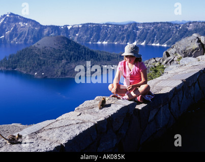 A young girl feeds a chipmunk or ground squirrel on the rim of Crater Lake - Stock Photo
