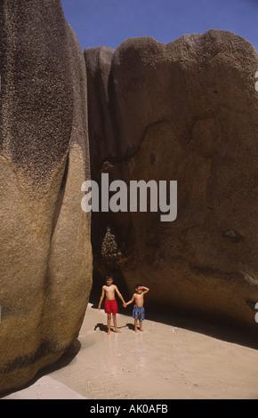 Two boys standing between massive granite rocks on Anse Source de Argent beach Seychelles - Stock Photo