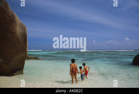 Mother and children on the Anse Source de Argent beach Seychelles - Stock Photo