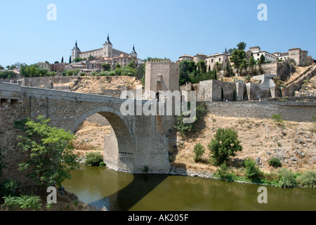 The Puerta de Alcantara on a bridge over the River Tagus with the Alcazar behind, Toledo, Castilla-La-Mancha, Spain - Stock Photo