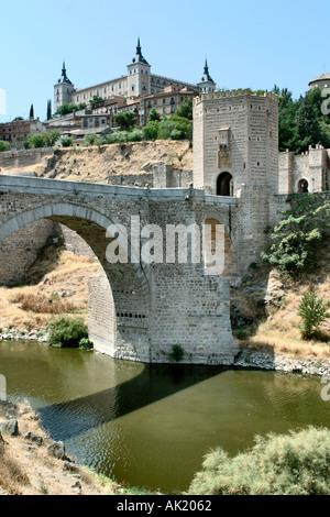 The Puerta de Alcantara on a bridge over the River Tagus with the Alcazar behind, Toledo, Castilla-La-Mancha, Spain - Stock Photo