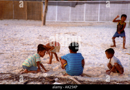 Filipino children playing on Boracay Beach at dusk in the Philippines. - Stock Photo