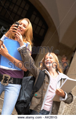 A young girl trying to snatch a mobile phone from another girl. - Stock Photo