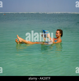 A single woman wearing brief bikini lying in semi-sitting position floating and reading a magazine on the Dead Sea - Stock Photo