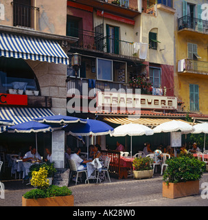Attractive cafes and restaurants and people dining under fringed sun umbrellas on the waterfront in Villefranche - Stock Photo