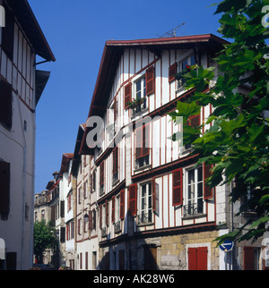 Traditional Basque architecture of white houses with terracotta coloured shutters in St Jean-de-Luz France - Stock Photo