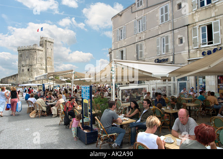 Pavement cafe in the Vieux Port with the Tour St Nicolas behind, La Rochelle, Poitou-Charentes, France - Stock Photo