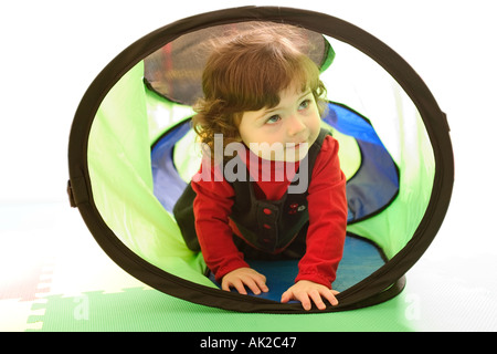 baby girl crawling through play tube - Stock Photo
