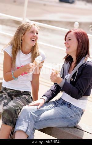 Two teenage girls eating ice creams - Stock Photo