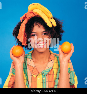 Studio portrait of smiling young woman holding orange in each hand. - Stock Photo