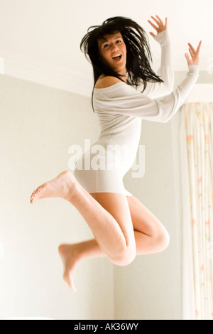 Girl jumping on bed - Stock Photo