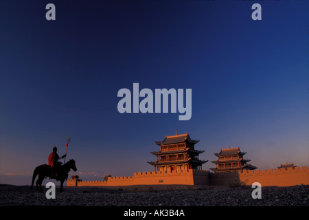 Soldier riding on horse guarding Jiayuguan Fortress western end of Great Wall at sunset Gansu Province China - Stock Photo