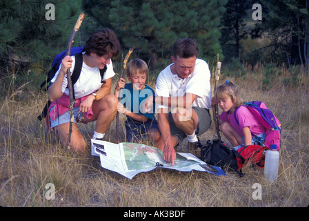released family hiking navigating using map and compass - Stock Photo