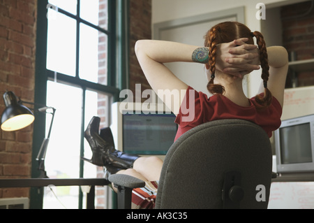 Red haired woman leaning back at her office desk - Stock Photo