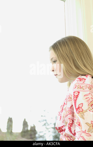 Profile of a teenage girl looking out a window - Stock Photo