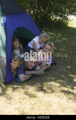 Family looking out of tent at campsite - Stock Photo
